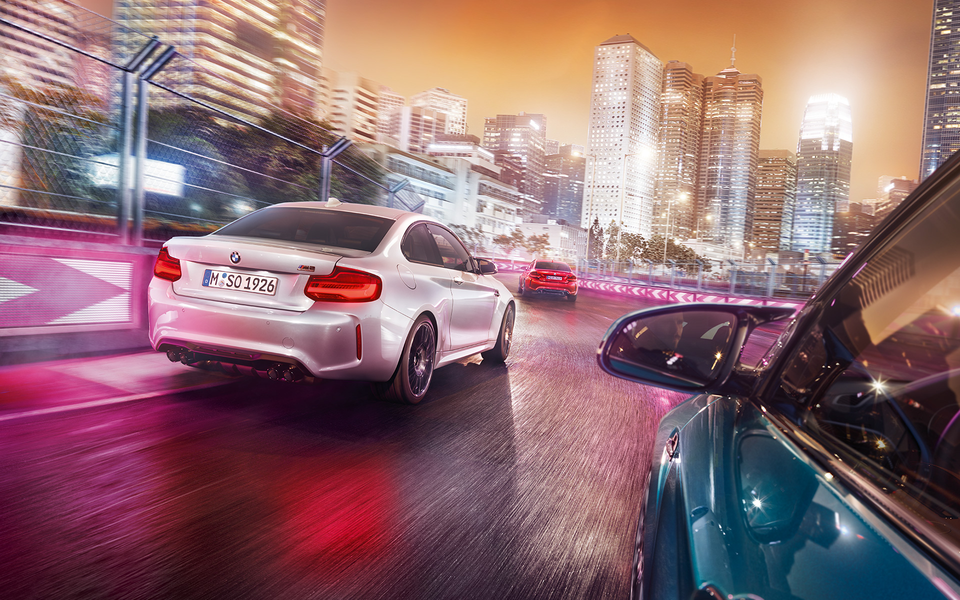 Three BMW M2 Competition in rear view driving on race track in front of illuminated skyline.