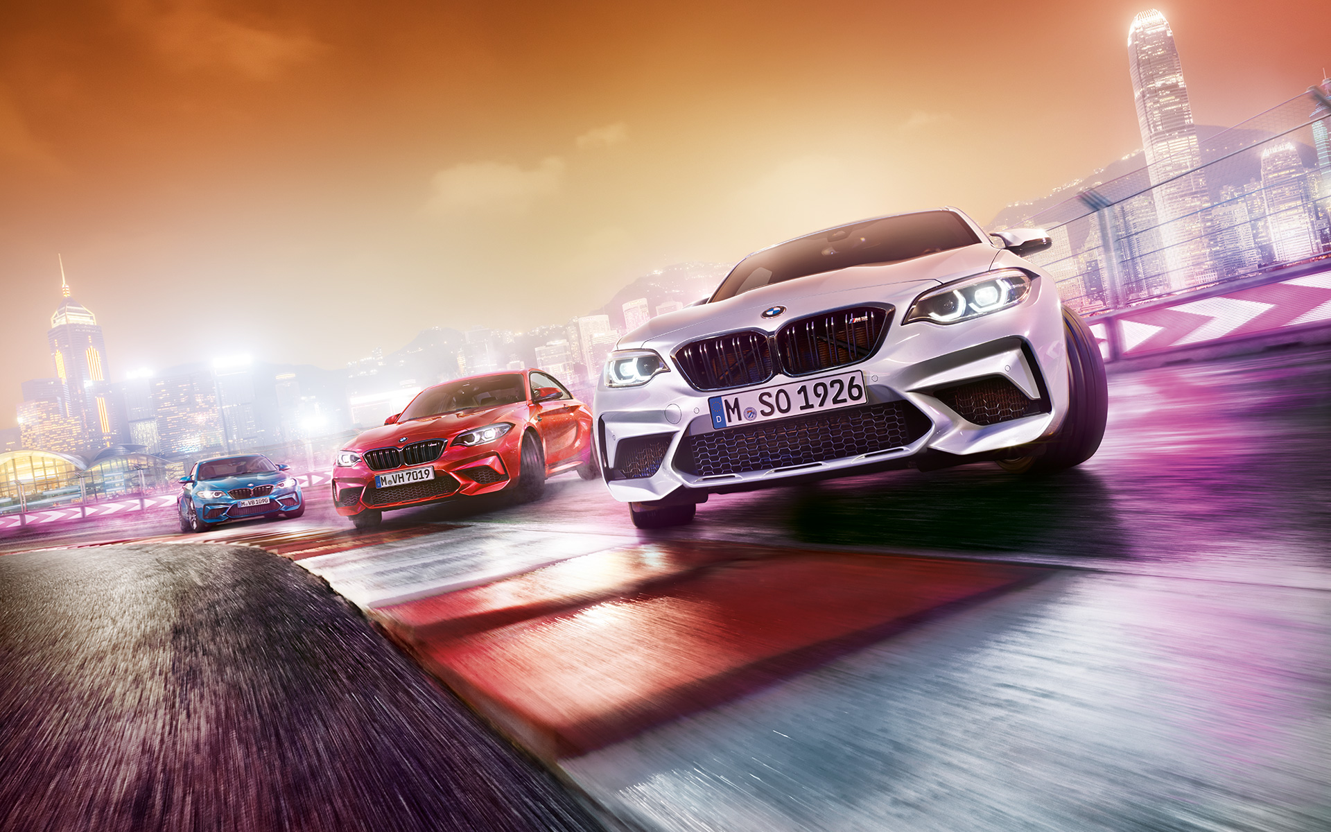 Three BMW M2 Competition drifting on race track in front of nocturnal cityscape.