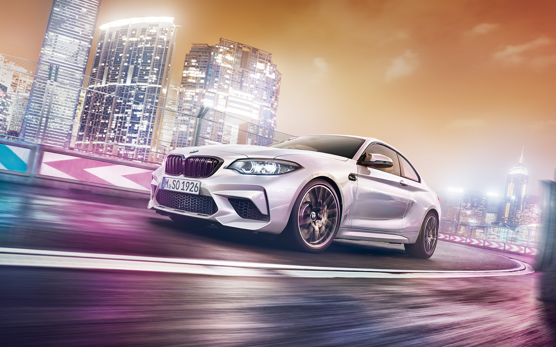 White BMW M2 Competition driving on race track in front of nocturnal skyline.